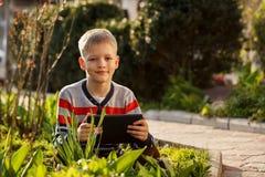 Muchacho feliz al aire libre usando su tableta para jugar imágenes de archivo libres de regalías