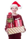 Muchacho feliz con el brazo lleno de regalos de la Navidad Fotografía de archivo libre de regalías