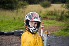 Muchacho feliz con el casco en el rastro del kart Fotografía de archivo libre de regalías