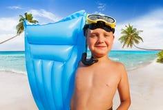 Muchacho feliz con el colchón en una Palm Beach Imagenes de archivo