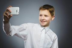 Muchacho feliz con el móvil o teléfono celular que hace el selfie en fondo gris Imágenes de archivo libres de regalías