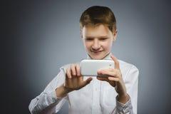 Muchacho feliz con el móvil o teléfono celular que hace el selfie en fondo gris imagen de archivo