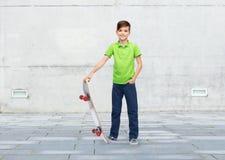 Muchacho feliz con el monopatín Foto de archivo libre de regalías