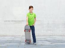 Muchacho feliz con el monopatín sobre fondo de la calle Fotos de archivo