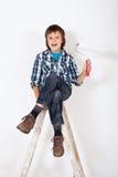 Muchacho feliz con el rodillo de pintura encima de la escalera Imágenes de archivo libres de regalías