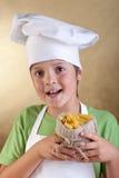 Muchacho feliz con el sombrero del cocinero que sostiene las pastas sin procesar en pequeño saco Fotos de archivo