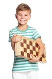Muchacho con el tablero de ajedrez Fotografía de archivo libre de regalías