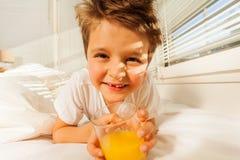 Muchacho feliz con el vidrio de jugo fresco en su dormitorio Imagen de archivo libre de regalías