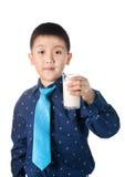 Muchacho feliz con el vidrio de leche a disposición aislado en el fondo blanco Fotos de archivo