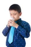 Muchacho feliz con el vidrio de leche a disposición aislado en el fondo blanco Fotografía de archivo libre de regalías