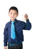 Muchacho feliz con el vidrio de leche a disposición aislado en el fondo blanco Imágenes de archivo libres de regalías