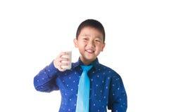 Muchacho feliz con el vidrio de leche a disposición en el backgroun blanco Imagen de archivo libre de regalías