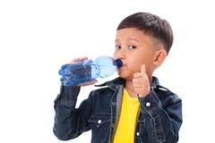 Muchacho feliz con la botella de agua y el mostrar de pulgar para arriba Imagen de archivo