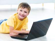 Muchacho feliz con la computadora portátil Fotografía de archivo libre de regalías
