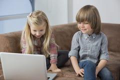 Muchacho feliz con la hermana que usa el ordenador portátil en el sofá Fotos de archivo