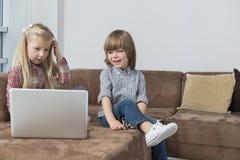 Muchacho feliz con la hermana que usa el ordenador portátil en el sofá Fotografía de archivo