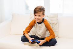 Muchacho feliz con la palanca de mando que juega al videojuego en casa Imagen de archivo