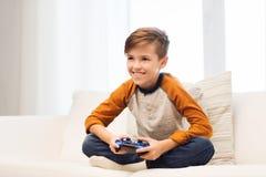 Muchacho feliz con la palanca de mando que juega al videojuego en casa Fotos de archivo libres de regalías