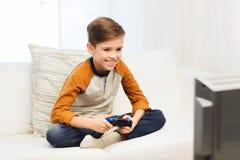 Muchacho feliz con la palanca de mando que juega al videojuego en casa Fotografía de archivo