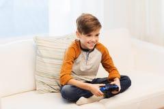 Muchacho feliz con la palanca de mando que juega al videojuego en casa Imágenes de archivo libres de regalías