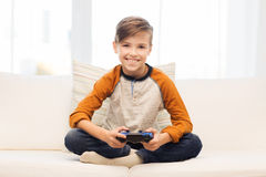 Muchacho feliz con la palanca de mando que juega al videojuego en casa Imagenes de archivo
