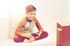 Muchacho feliz con la palanca de mando que juega al videojuego en casa Fotos de archivo