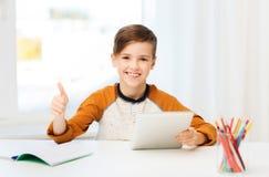 Muchacho feliz con la PC de la tableta que muestra los pulgares para arriba en casa Fotografía de archivo