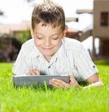 Muchacho feliz con la tableta al aire libre Imagen de archivo libre de regalías