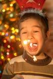 Muchacho feliz con las bengalas de la Navidad Foto de archivo
