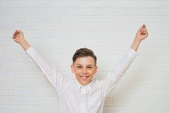 Muchacho feliz con las manos aumentadas para arriba que celebra la victoria Imagen de archivo libre de regalías