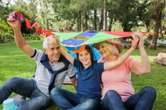 Muchacho feliz con los abuelos que sostienen la cometa en Imagen de archivo
