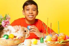 Muchacho feliz con los huevos y el conejo de Pascua en la tabla Foto de archivo libre de regalías