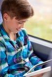 Muchacho feliz con PC de la tableta en autobús o tren del viaje Imágenes de archivo libres de regalías