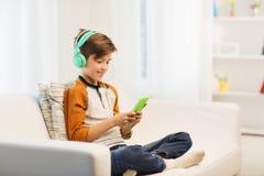 Muchacho feliz con smartphone y los auriculares en casa Fotografía de archivo libre de regalías