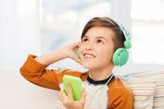Muchacho feliz con smartphone y los auriculares en casa Fotos de archivo libres de regalías
