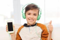 Muchacho feliz con smartphone y los auriculares en casa Fotografía de archivo