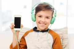 Muchacho feliz con smartphone y los auriculares en casa Foto de archivo libre de regalías
