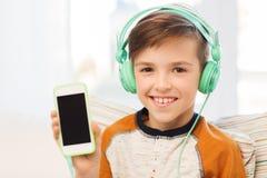 Muchacho feliz con smartphone y los auriculares en casa Fotos de archivo