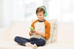 Muchacho feliz con smartphone y los auriculares en casa Imagen de archivo