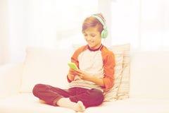 Muchacho feliz con smartphone y los auriculares en casa Imagen de archivo libre de regalías