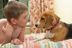 Muchacho feliz con su perro que miente en un sofá en casa Foto de archivo libre de regalías
