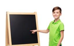 Muchacho feliz con tiza y la pizarra en blanco de la escuela Foto de archivo