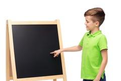 Muchacho feliz con tiza y la pizarra en blanco de la escuela Imagen de archivo libre de regalías