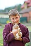 Muchacho feliz con un conejo Foto de archivo