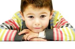 Muchacho feliz de 6 años que se inclina adelante con el fondo blanco Foto de archivo libre de regalías