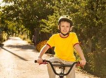 Muchacho feliz del adolescente que monta con seguridad la bicicleta en el campo Foto de archivo