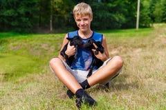 Muchacho feliz del adolescente que sostiene pequeñas cabras negras del bebé en el prado Foto de archivo
