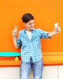 Muchacho feliz del adolescente que toma el autorretrato de la imagen en smartphone Imagenes de archivo