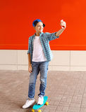 Muchacho feliz del adolescente que toma el autorretrato de la imagen en smartphone en ciudad Foto de archivo