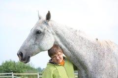 Muchacho feliz del adolescente y caballo blanco en el campo Imagen de archivo